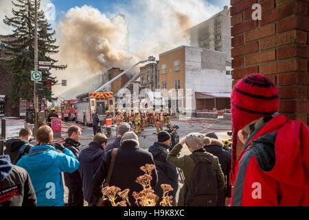 Montréal, CA - 23 Nov 2016: les piétons et media watch les pompiers travaillent sur 'Cafe Amusement 68' bâtiment Banque D'Images
