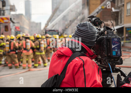 Montréal, CA - 23 Nov 2016: Un caméraman filme les pompiers qui travaillent sur 'Cafe Amusement 68' bâtiment en Banque D'Images