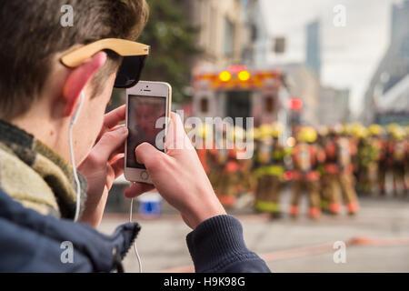 Montréal, ca - 23 nov 2016: piétons mâles prend des photos avec le smartphone comme les pompiers travaillent sur Banque D'Images