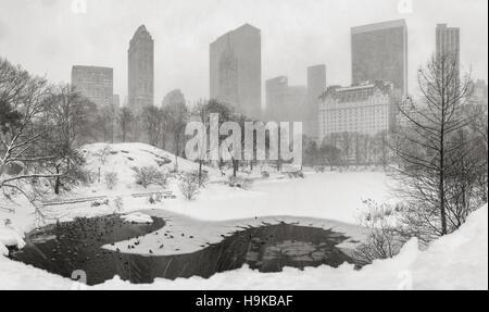 Étang gelé et les fortes chutes de neige dans Central Park avec une vue panoramique de grattes-ciel de Manhattan. Midtown, New York City (B&W)