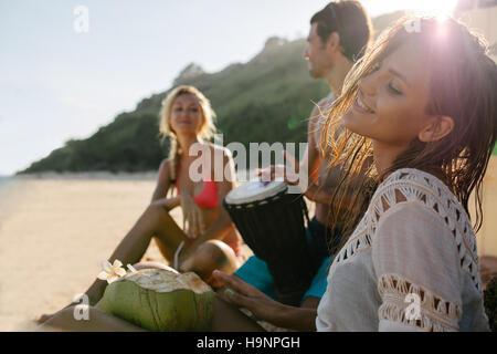 Jeune femme de détente sur le bord de la mer avec ses amis dans l'arrière-plan. Les amis à faire la fête et s'amuser sur la plage.