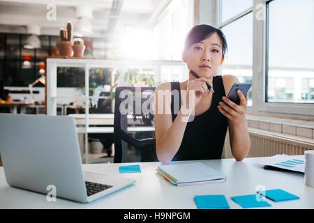 Portrait of asian woman assise à son bureau avec téléphone mobile. Asian businesswoman working in office. Banque D'Images