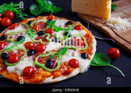 Des pizzas au salami, olives noires et basilic sur un fond noir. Banque D'Images