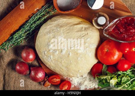 Ingrédients pour des pizzas: pâte, tomates, oignons, herbes, huile d'olive. Focus sélectif. Banque D'Images