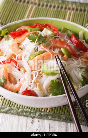Salade thaï avec des nouilles de verre, les crevettes et les légumes dans un bol close-up vertical. Banque D'Images
