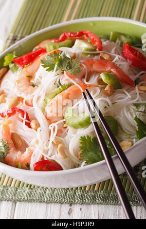 Salade thaï avec des nouilles de verre, de crevettes et d'arachides dans un bol close-up vertical. Banque D'Images