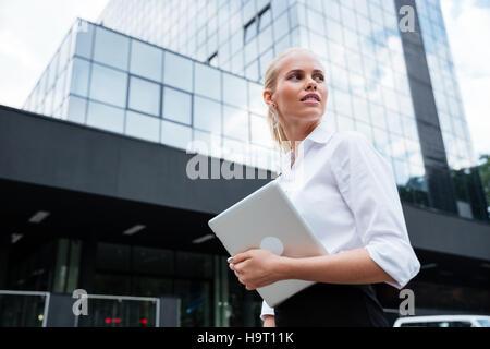 Femme d'affaires travaillant avec la tablette à l'extérieur, debout près de l'office