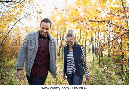 Smiling couple walking in autumn woods Banque D'Images