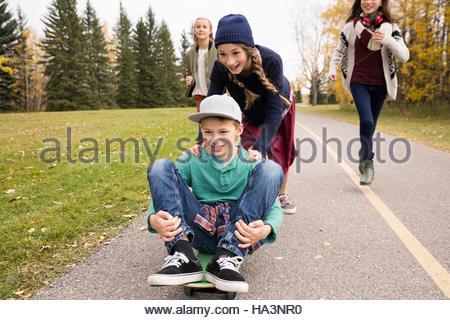 Entre garçon et filles skateboarding sur chemin dans autumn park Banque D'Images