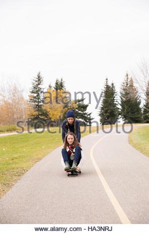 Le Tween girls skateboarding sur path in autumn park Banque D'Images