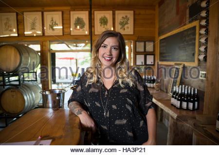 Confident female portrait viticulteur présentoirs de comptoir dans la salle de dégustation cave Banque D'Images