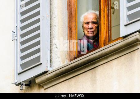 Une vieille dame italienne regarde par sa fenêtre en Citta Alta, Bergame, Italie Banque D'Images