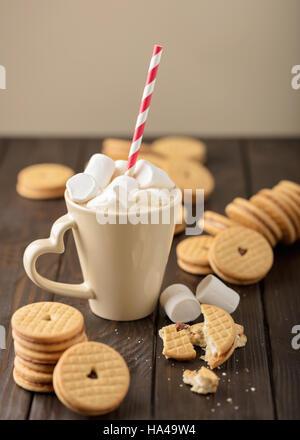 Les guimauves dans une tasse avec les cookies avec des cœurs de la confiture. Banque D'Images