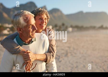 Portrait of happy young man carrying sa belle épouse sur son dos à la plage. Être libre de profiter de leurs vacances Banque D'Images