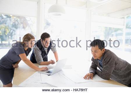 Architectes avec portable rédaction et révision des blueprints in office Banque D'Images