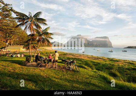 Les personnes ayant un pique-nique face au lagon, l'île Lord Howe, NSW, Australie, avec Mt Gower et Mt Lidgbird Banque D'Images
