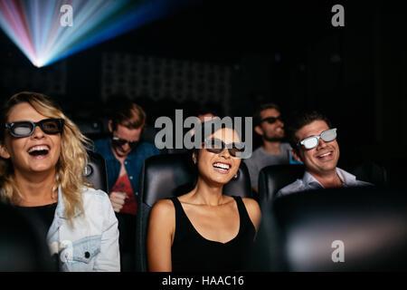 Groupe de jeunes amis regarder des films en 3d dans le théâtre et de rire. Les jeunes hommes et femmes portant des Banque D'Images