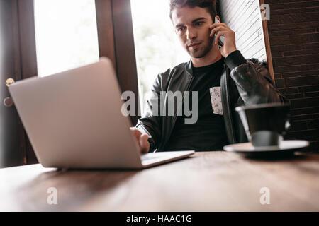 Handsome man sitting in cafe table avec tasse de café à l'aide de téléphone mobile et ordinateur portable. Banque D'Images