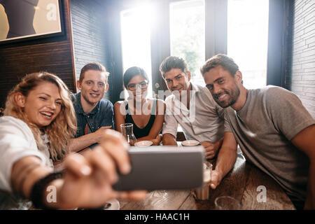Petit groupe d'amis en tenant sur un selfies téléphone mobile. Les jeunes hommes et les femmes siégeant ensemble Banque D'Images