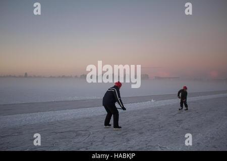 Père et fils de hockey sur glace de la formation d'un lac gelé avec une ville de brouillard à l'arrière-plan. Banque D'Images