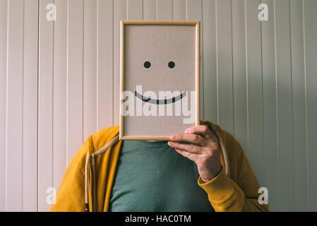Mettre un visage heureux, sur le bonheur et les émotions gaies concept, man holding photo frame avec imprimé émoticône Banque D'Images