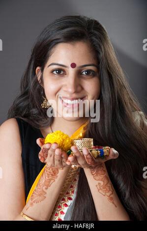 Une fille souriante et tenant une lampe à huile traditionnelle Diwali diya avec fleur offrande religieuse et souriant Mumbai Inde
