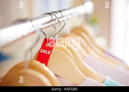 Tag vente rouge sur cintre avec robe ou chemisier. Banque D'Images