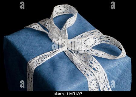 Gros plan sur white lace ribbon bow nouée de l'enveloppé dans du papier texturé bleu sur fond noir cadeaux Banque D'Images