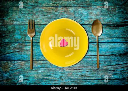 Forme de coeur rouge sur jaune plaque vide avec fourchette et cuillère de table en bois vintage bleu pour l'amour Banque D'Images