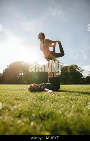 Jeune couple solide paire de plein air en faisant du yoga. L'homme et femme d'équilibrage de levage en position Banque D'Images