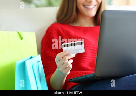 Gros plan d'une fille main tenant une carte de crédit et l'achat en ligne avec un ordinateur portable ou un sac Banque D'Images