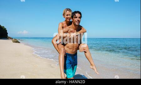 Portrait of handsome young man carrying girlfriend sur son dos et marcher le long de la côte. Couple enjoying piggyback Banque D'Images