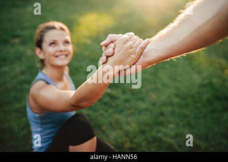 Gros plan de l'homme femme aidant à se lever. Se concentrer sur les mains du couple exercising at park. Banque D'Images