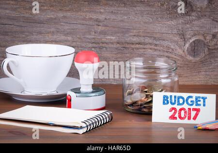 Le budget de 2017 - les affaires financières, concept. L'argent dans le verre sur une table en bois. texture background Banque D'Images