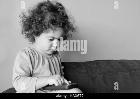 Enfant fille (2 ans) joue sur téléphone mobile est assis sur un canapé à la maison.