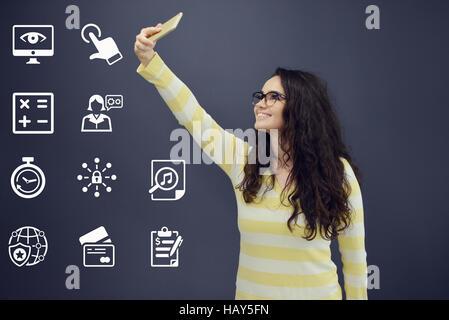 Femme avec prise de téléphone en face de selfies avec arrière-plan graphique d'affaires établi. Banque D'Images