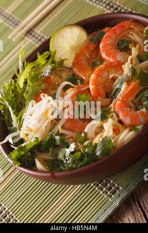 Soupe laksa malais aux gambas close up dans un bol sur la table. La verticale Banque D'Images