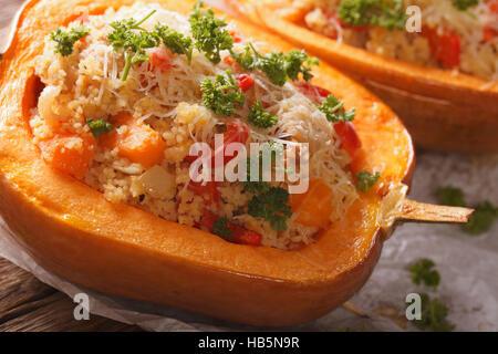 Citrouille farcie au couscous cuit, la viande et les légumes sur la table macro horizontale. Banque D'Images