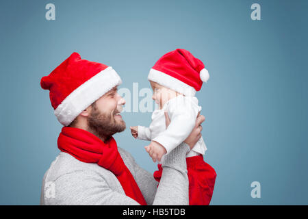 Avec son père baby boy wearing Santa hats celebrating Christmas Banque D'Images
