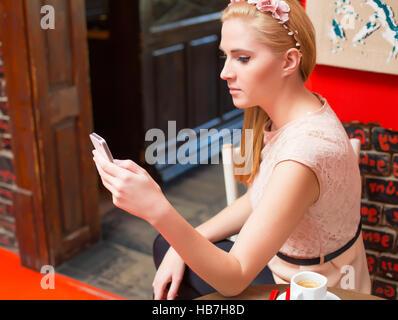 Femme blonde en utilisant son mobile à l'envoi de sms. Banque D'Images