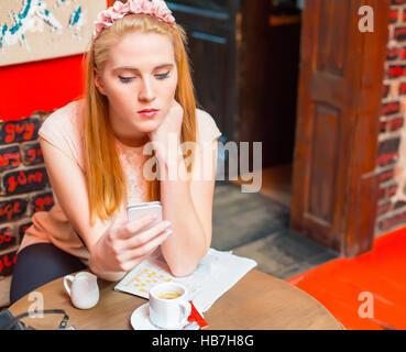 Femme blonde en utilisant sa pub smart phone en cours sur les médias sociaux. Banque D'Images