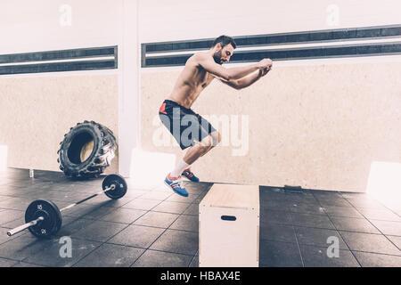Jeune homme sautant sur fort à l'entraînement en salle de sport Banque D'Images