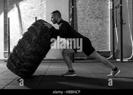Bodybuilder beau solide tenant un énorme tire Banque D'Images