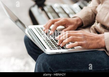 Portrait of young African man with laptop assis sur un banc en bois et taper. Banque D'Images