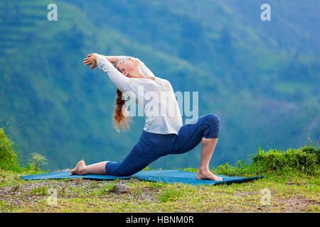 Mettre en place des pratiques sportives femme yoga asana Anjaneyasana en montagne Banque D'Images