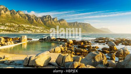 Camps Bay Ocean piscine au coucher du soleil avec la ville et les montagnes derrière Banque D'Images