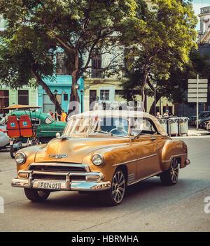 L'heureux propriétaire de cette voiture classique de couleur d'or voyage le long d'une rue à sens unique à La Havane, Banque D'Images