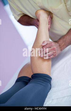 Physiothérapeute massage des jambes donnant à une femme