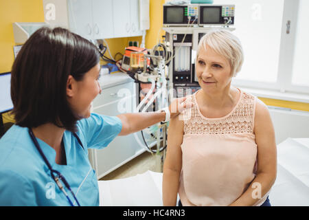 Femme médecin un patient consolant Banque D'Images
