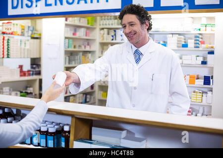 Pharmacien donnant bouteille de pilules au client Banque D'Images